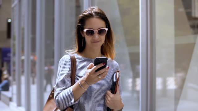 Young beautiful businesswoman in sunglasses holding documents and using smartphone, walking in the street. Slow motion video