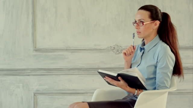 Young beautiful businesswoman thinking with a folder in hands video