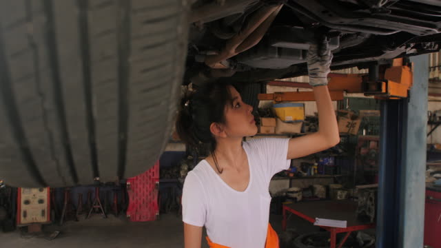 Young beautiful car mechanic inspects the car undercarriage way in garage, car service concept. dolly shot Auto Repair Shop, Women, Adult, Females, Mechanic handbook stock videos & royalty-free footage