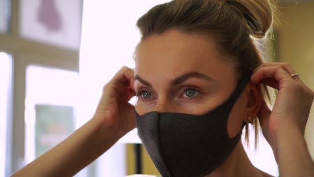 stockvideo's en b-roll-footage met jonge mooie kaukasische vrouw die op zwart beschermend gezichtsmasker wordt gezet dat in grote spiegel tijdens coronavirus covid-19 wordt weerspiegeld - fitnessleraar
