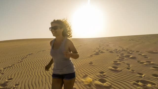 young beautiful caucasian woman running on the desert dunes in outdoor happy leisure activity. happiness and freedom concept for people in summer time - 40 44 lata filmów i materiałów b-roll