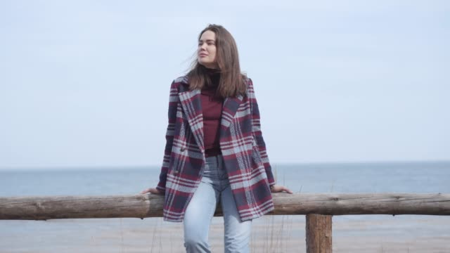 Young beautiful Caucasian woman sitting on wooden fence on river bank. Portrait of thoughtful cute lady in plaid jacket and jeans resting alone near the water on sunny day. Lifestyle, leisure.