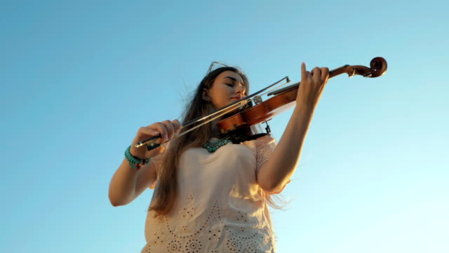 Young beautiful caucasian woman  wearing jeans plays violin staying on the beach near the beautiful sea or ocean, Slow motion video