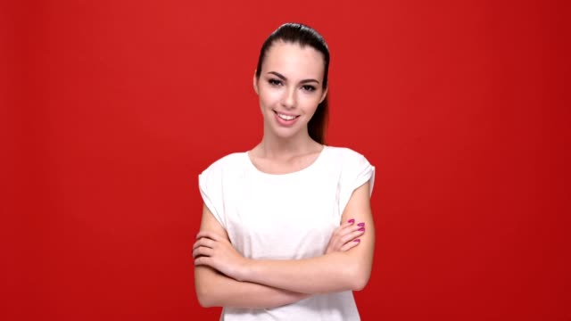 Young beautiful caucasian woman with arms crossed smiling over red background. video