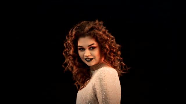 stockvideo's en b-roll-footage met jonge mooie kaukasische vrouw met lang krullend haren weg terug en front met haar haren ontwikkelen op een zwarte achtergrond. - curly brown hair