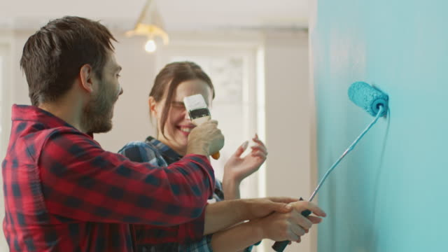 vídeos de stock e filmes b-roll de young beautiful couple decorate their new apartment and fool around. husband and wife are painting the wall with rollers that are dipped in light blue paint. they are happy and have fun. renovations at home. - melhoria