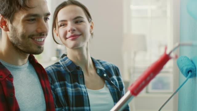 unga vackra paret inreda sin nya lägenhet. man och hustru målar väggen med valsar som är doppad i ljus blå färg. de är happy. flickan ger man en kyss. renoveringar hemma. - painting wall bildbanksvideor och videomaterial från bakom kulisserna