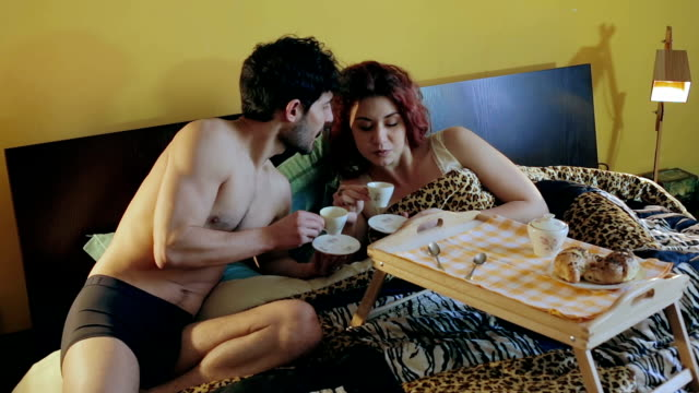 young beautiful couple having breakfast in bed: relationship, love, morning video