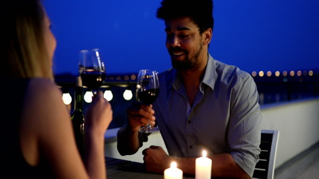 Young beautiful couple having romantic dinner on rooftop video
