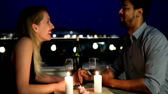 young beautiful couple having romantic dinner on rooftop - data scritta video stock e b–roll