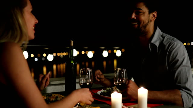 vídeos de stock e filmes b-roll de young beautiful couple having romantic dinner on rooftop - namorar