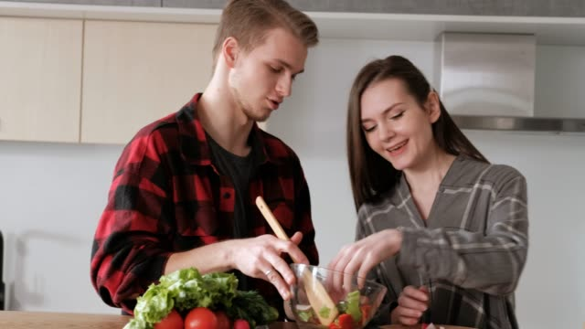 Young beautiful couple in plaid shirts are cooking at home in the kitchen. A woman and a man cut vegetables and make a salad of pepper, tomato, radish in a transparent glass dish.