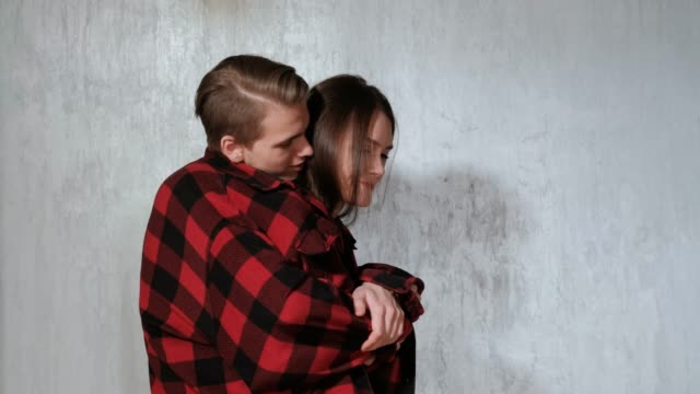 Young beautiful couple, man and woman, are tenderly embracing against the gray wall of the house.