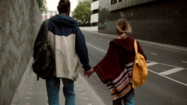 Young beautiful couple with backpack walking in the evening near the road. Man and woman spending time together video