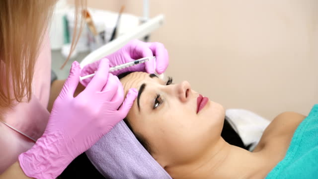Bидео Young beautiful dark-haired woman gets rejuvenating facial injections.