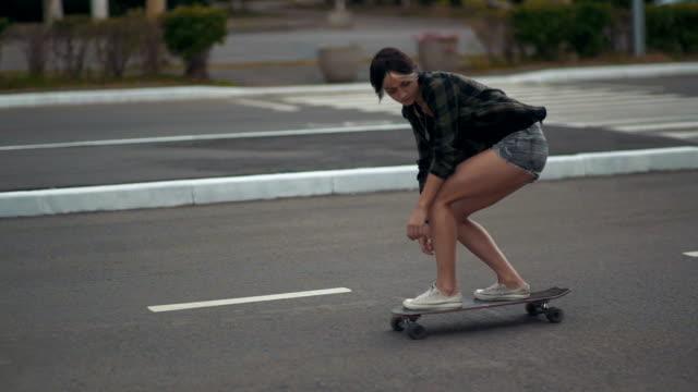 Jovem hippie feminina linda andando na rua no skate ou longboard no dia - vídeo