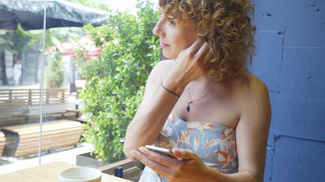 stockvideo's en b-roll-footage met jonge mooie vrouw luisteren naar muziek. - blond curly hair