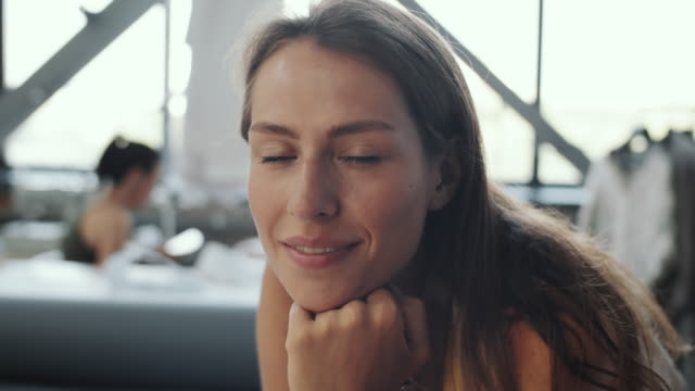 vídeos de stock e filmes b-roll de young beautiful female tailor smiling and posing for camera at work - trabalho de design
