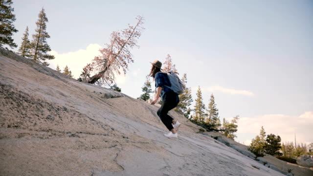 vídeos y material grabado en eventos de stock de joven hermosa turista con la mochila solo caminatas, escalar una roca gigante en el parque nacional de yosemite lenta. - escalada en rocas