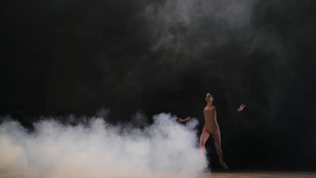 junge schöne mädchen tänzer springen hoch auf rauch dunkelbühne während leistung. ballerina in modernen kostümen tanzen sinnlich in szene. epische sprung. slow-motion - ballettröckchen stock-videos und b-roll-filmmaterial