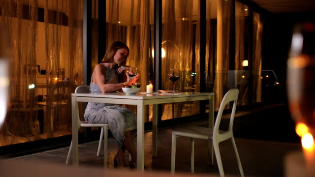 Young beautiful girl drinks wine alone in a posh restaurant and waits for her boyfriend video