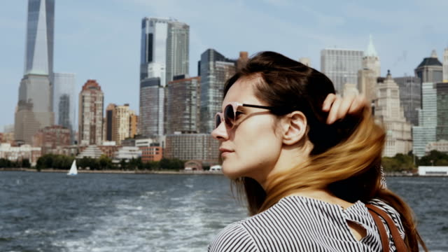 Young beautiful girl go for a boat through the East river in New York, America. Happy tourist on excursion in sunny day video