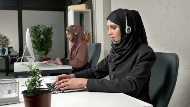 A young beautiful girl in a black hijab is talking on the headset, answering calls in call center. Arab women in the office. 60 fps video