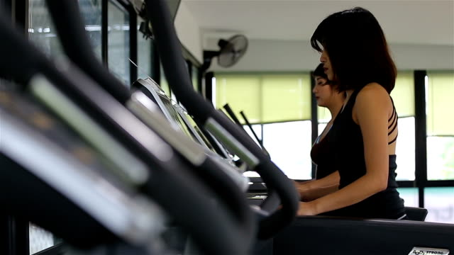 Young beautiful girl in a gym, running on a running simulator, then drinking water video