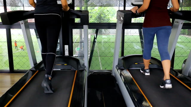 Young beautiful girl in a gym, running on a running simulator video
