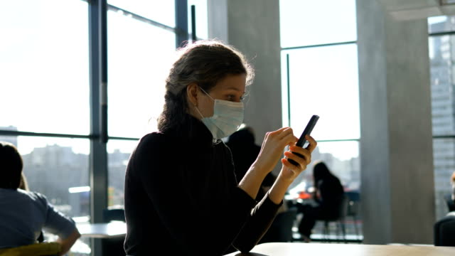 A young beautiful girl in a medical mask is sitting with a phone in a shopping center - vídeo
