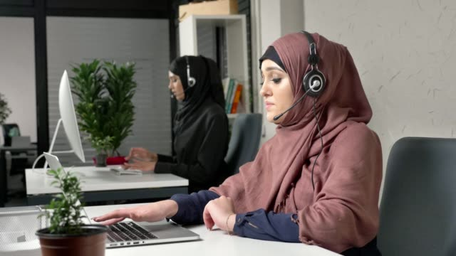 A young beautiful girl in a pink hijab is talking on the headset, answering calls in call center. Arab women in the office. 60 fps video