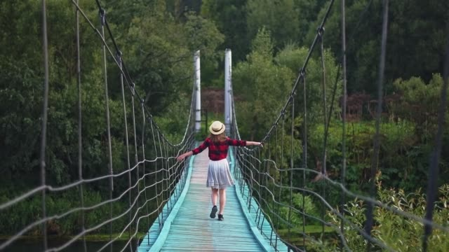 A young, beautiful girl in a skirt and shirt walks on a suspended wooden bridge.