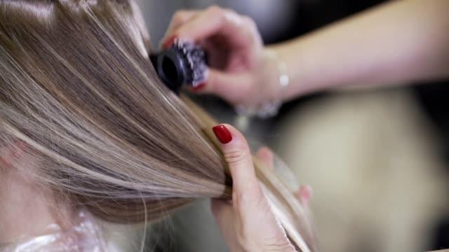 vidéos et rushes de jeune belle fille dans le salon de beauté. coiffeur styliste fait cheveux de fille - soins capillaires