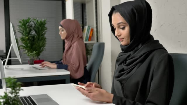 Young beautiful girl in black hijab sits in office and uses smartphone. Girl in black hijab in the background. Arab women in the office. 60 fps video
