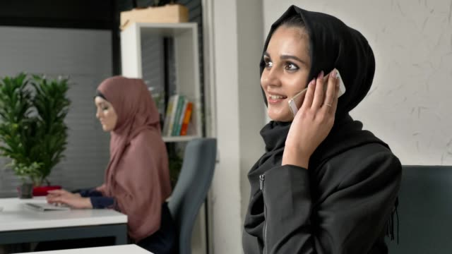 Young beautiful girl in black hijab sits in the office and speaks on the smartphone. 60 fps video