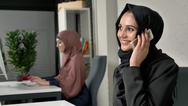 Young beautiful girl in black hijab sits in the office smiling and speaks on the smartphone. 60 fps video