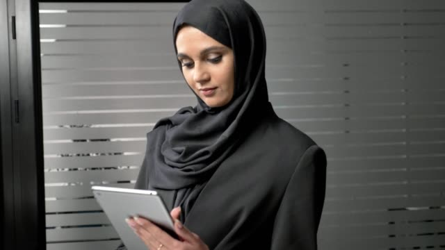 A young beautiful girl in black hijab uses a tablet, looks at photos. Arab women in the office. 60 fps video