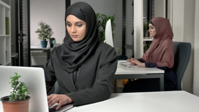 Young beautiful girl in black hijab working at office on computer. Smiling and looking at the camera. Girl in red hijab in the background. 60 fps video