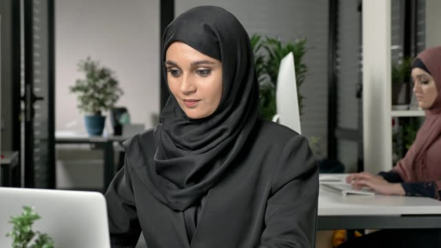 Young beautiful girl in black hijab working at office on computer. Smiling and looking at the camera. Girl in red hijab in the background. Close up 60 fps video