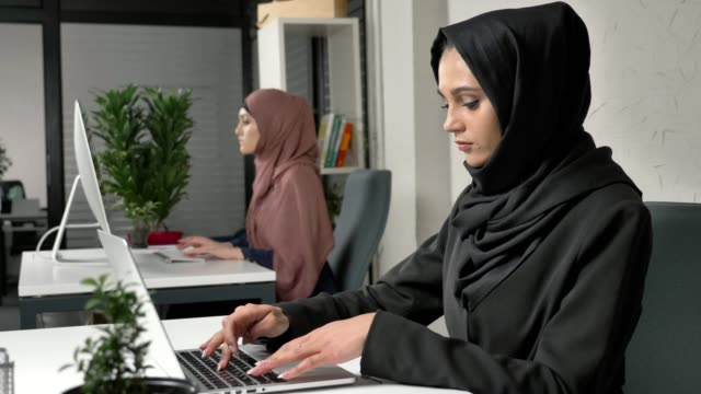 Young beautiful girl in black hijab working on laptop in office, massages his whiskey, migraine, headache. Woman in pink hijab in the background. 60 fps video