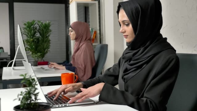 Young beautiful girl in black hijab working on laptop in office, drinking tea, coffee. Woman in pink hijab in the background. 60 fps video