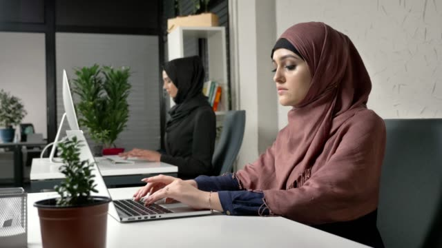 Young beautiful girl in pink hijab and glasses typing, working on computer. Look at the camera, smiling. Arab women in the office. Girl in black hijab in background. 60 fps video