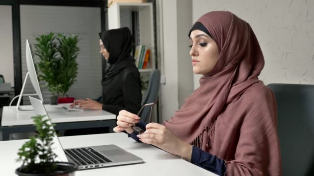 Young beautiful girl in pink hijab puts on glasses and starts working on the computer. Arab women in the office 60 fps video