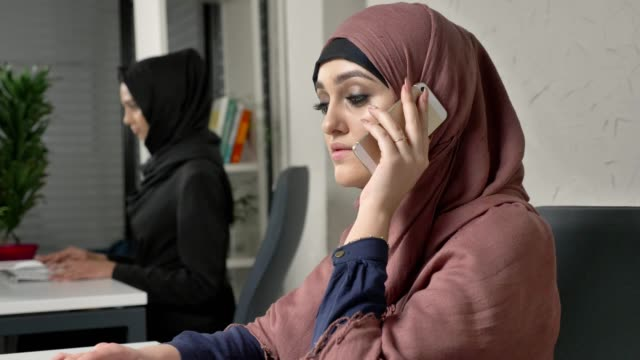 Young beautiful girl in pink hijab sits in the office and speaks on the smartphone. 60 fps video