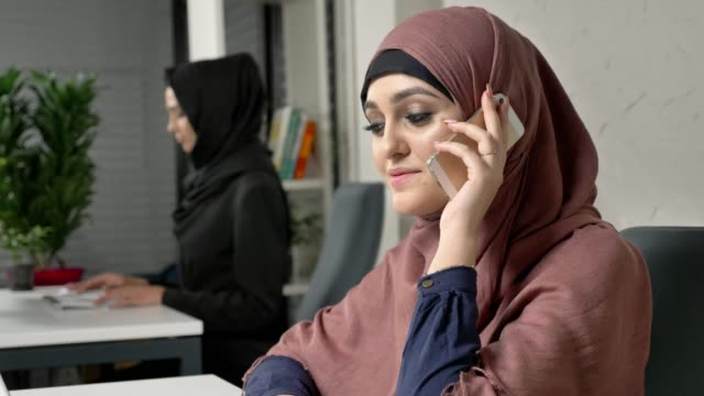 Young beautiful girl in pink hijab sits in the office and speaks on the smartphone, laughing. 60 fps video