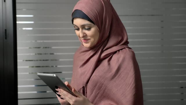 A young beautiful girl in pink hijab uses a tablet, looks at photos, smiling. Arab women in the office. 60 fps video