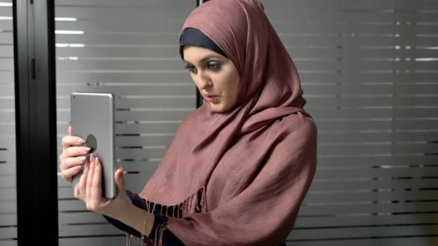 A young beautiful girl in pink hijab uses a tablet, speaks in a video chat, greeting. 60 fps video