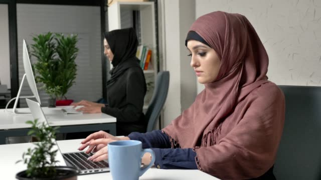 Young beautiful girl in pink hijab working on laptop in office, drinking tea, coffee. Woman in black hijab in the background. 60 fps video