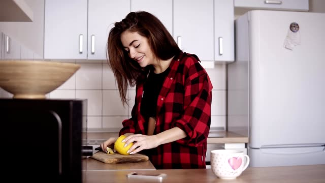 Young beautiful girl in red flannel shirt slicing lemon and then making herself a cup of tea in the kitchen. video