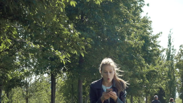Young beautiful girl is walking in the park with a smartphone. Reads the message and is very happy. Dancing and bouncing with happiness and joy. Young beautiful girl is walking in the park with a smartphone. Reads the message and is very happy. Dancing and bouncing with happiness and joy. Slow motion desire stock videos & royalty-free footage